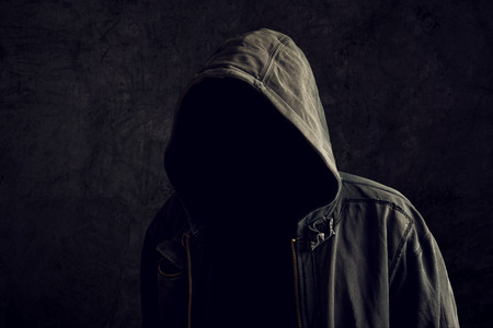 Faceless unknown and unrecognizable man without identity wearing hood in dark room, spooky criminal person.