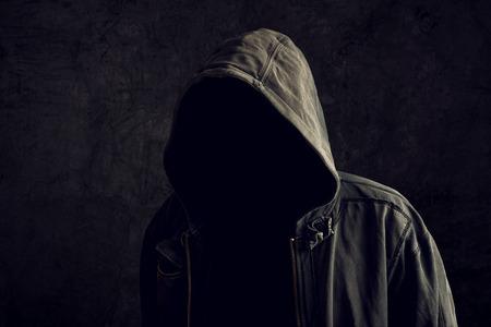 Faceless onbekende en onherkenbare man zonder identiteit dragen kap in een donkere kamer, griezelige crimineel persoon. Stockfoto