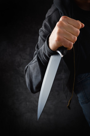 holding a knife: Evil criminal with large sharp knife ready for robbery or to commit a homicide Stock Photo