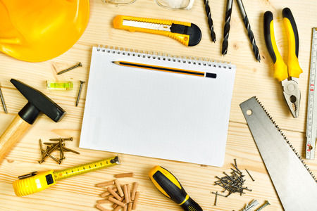 timeframe: Planning a Project in Carpentry and Woodwork Industry, Notebook and Assorted Woodwork and Carpentry Tools  on Pinewood Workshop Table. Stock Photo