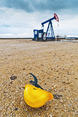 pozo petrolero: Casco de protección y Pumpjack Oil Pump funcionen con gas natural en el campo de bombeo del pozo de petróleo.