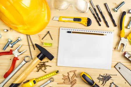 Planning a Project in Carpentry and Woodwork Industry, Notebook and Assorted Woodwork and Carpentry Tools  on Pinewood Workshop Table. Stock Photo