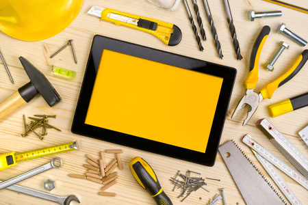 tool: Digital Tablet and Assorted Woodwork and Carpentry Tools  on Pinewood Workshop Table Stock Photo