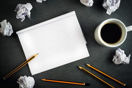 persona escribiendo: Concepto Escritura Creativa Con Los L�pices, Taza de caf�, Bloc de notas y papel arrugado en la tabla, vista superior.