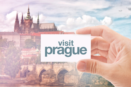 tour operator: Tourist Agent Holding Business Card with Visit Prague Message, Famous Sightseeings of Czech Capital -  Castle and Charles Bridge in Background.