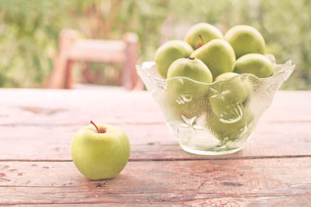 wellfare: Fresh green apples on wooden table in the garden, vintage instagram like toned image. Stock Photo