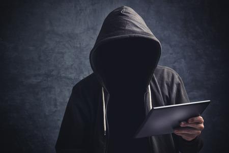 Gezichtsloze onbekend onherkenbaar anonieme man met digitale tablet computer surfen op internet.