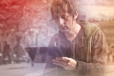 news update: Adult Caucasian Man Reading News on Digital Tablet Computer Device. Stock Photo