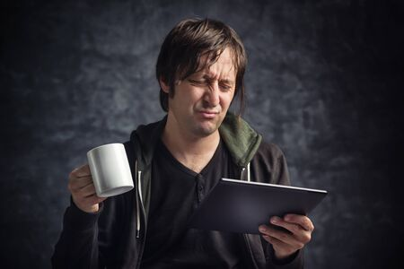 bad news: Adult Caucasian Man Reading Bad News on Digital Tablet Computer Device and Drinking Coffee Stock Photo