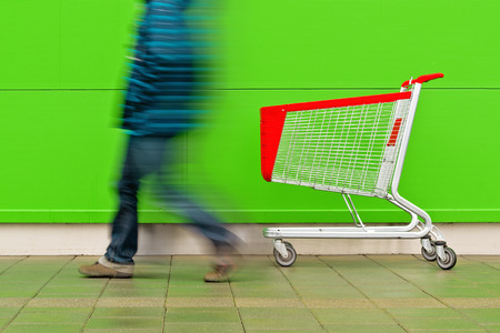 consumerism: Motion Blur Man Walking by Empty Shopping Cart Trolley in front of a Shopping Mall as Consumerism Concept Background.