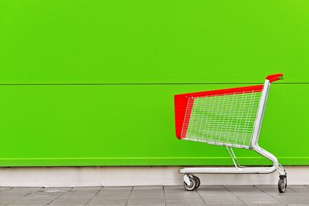 empty shopping cart: Empty Shopping Cart Trolley in front of Shopping Mall with Blank Copy Space as Consumerism Concept Background. Stock Photo