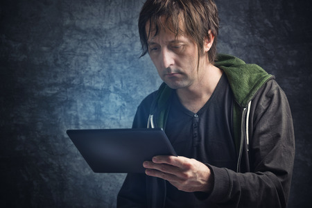 periodical: Adult Caucasian Man Reading News on Digital Tablet Computer Device. Stock Photo