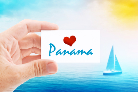 holiday message: Summer Vacation on Panama Beach, Person Holding Visiting Card for Summertime Holiday Message Love Panama and Sailboat at Sea in Background.