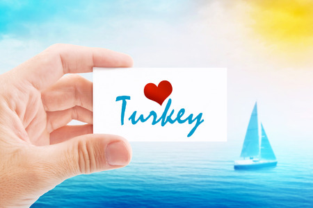 holiday message: Summer Vacation on Turkish Beach, Person Holding Visiting Card for Summertime Holiday Message Love Turkey and Sailboat at Sea in Background.