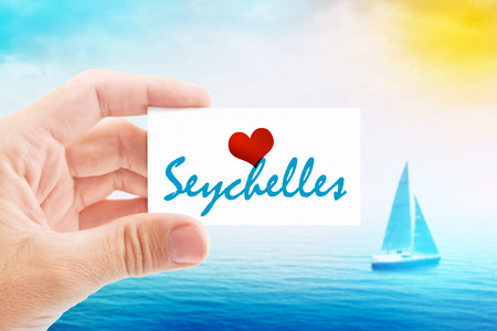 holiday message: Summer Vacation on Seychelles Beach, Person Holding Visiting Card for Summertime Holiday Message Love Seychelles and Sailboat at Sea in Background. Stock Photo