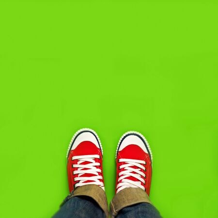 new beginnings: Springtime Youth Lifestyle Concept for New Beginnings, Woman with Red Sneakers Standing on Green Spring Background as Blank Copy Space. Stock Photo