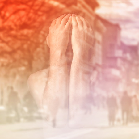 alone in crowd: Sad man is covering his face with hands and crying in despair, double exposure image with unrecognizable people walking on street.