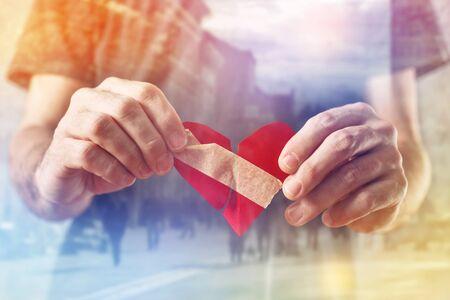 the human heart: Hombre Broken hearted como San Valent�n concepto de d�a, hombre que sostiene el coraz�n roto en las manos, el enfoque selectivo con poca profundidad de campo.