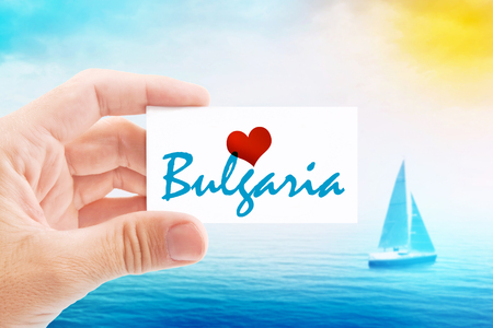 holiday message: Summer Vacation on Bulgaria Beach, Person Holding Visiting Card for Summertime Holiday Message Love Bulgaria and Sailboat at Sea in Background.