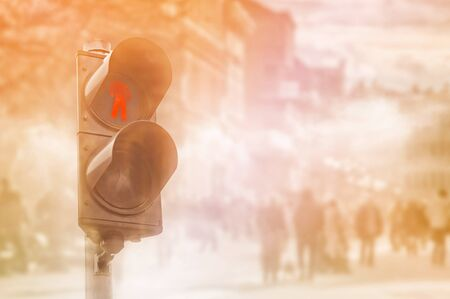 unrecognizable people: Red traffic light for pedestrians, double exposure image with unrecognizable people walking the street in background.