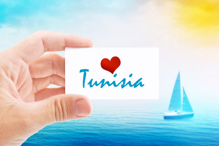 holiday message: Summer Vacation on Tunisia Beach, Person Holding Visiting Card for Summertime Holiday Message Love Tunisia and Sailboat at Sea in Background.