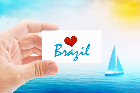 brazil beach: Summer Vacation on Brazil Beach, Person Holding Visiting Card for Summertime Holiday Message Love Brazil and Sailboat at Sea in Background.