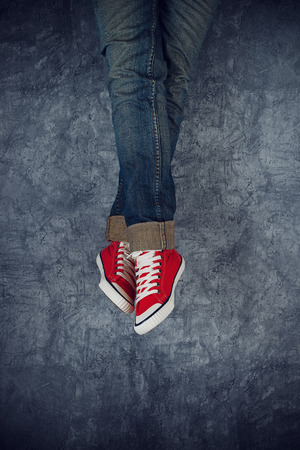 boyhood: Lazy Young Teenage Woman Relaxing Concept, Red Sneakers on grunge Background