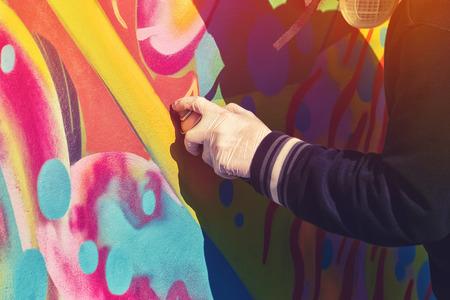 grafitis: Var�n adulto Graffiti pintura del artista Rociar el Muro, urbana Street Art Concept, Imagen virada con enfoque selectivo
