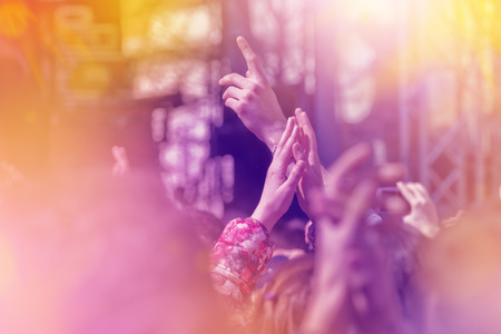festival: Fans Applauding To Music Band for Live Performing a Concert on Stage in Open Arena, Selective Focus Toned Image with Sunflares. Stock Photo