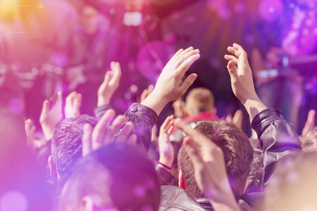 people clapping: Fans Applauding To Music Band for Live Performing a Concert on Stage in Open Arena, Selective Focus Toned Image with Sunflares. Stock Photo