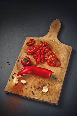 zesty: Red Hot Chili Pepper, Spice and Organic Garlic on Wooden Kitchen Plate as Hot Food Ingredients for Spicy Piquant Cuisine.