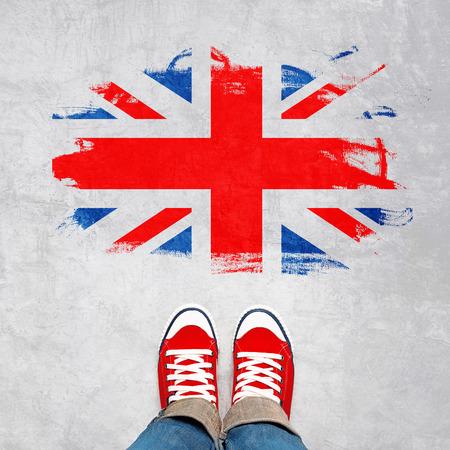great britain flag: British Urban Youth Concept, Feet in Red Sneakers from Above Standing in front of Grunge Great Britain Flag.