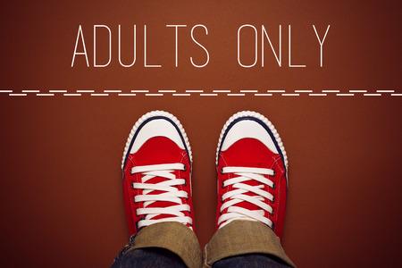 no pase: Sólo con adultos Concepto, joven adolescente Persona en Red Sneakers Permanente en Línea divisoria del área restringida. Foto de archivo