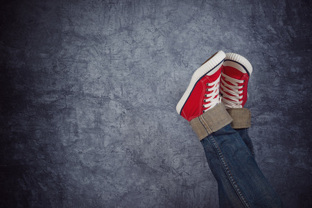Lazy Young Teenage Vrouw Ontspannen Concept, rode sneakers op grunge achtergrond Stockfoto