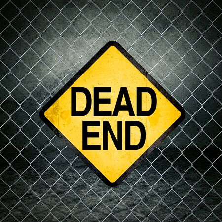 Dead End Grunge Yellow Warning Sign on Chainlink Fence of Industrial Warehouse photo
