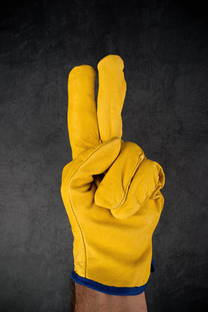 enact: Male Hand in Yellow Leather Construction Engineer or Builder Working protective Gloves Making Two Fingers Gesture.