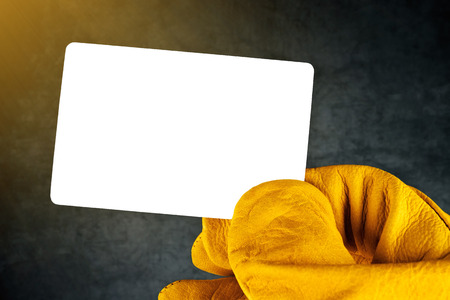 syndicate: Male Hand in Yellow Leather Construction Working Protective Gloves Holding Horizontal Blank Business Card with Rounded Corners.