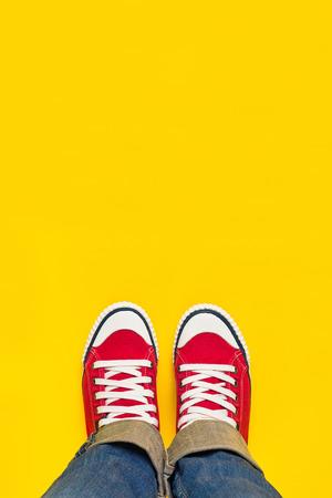 フィート上からコンセプト、赤黄色の背景、B に立っているスニーカーで 10 代の人; 痩せ細ったコピー スペース前に。