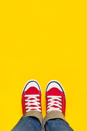 Feet From Above Concept, Teenage Person in Red Sneakers Standing on Yellow Background, B;lank Copy Space in Front.