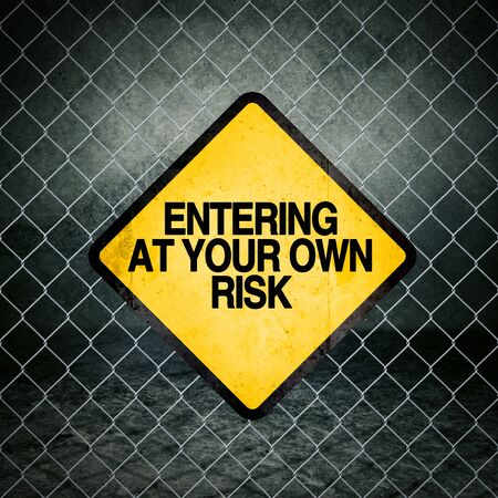chainlink fence: Entering at Your Own Risk Grunge Yellow Warning Sign on Chainlink Fence of Industrial Warehouse Stock Photo