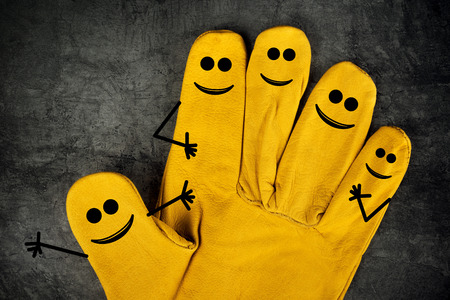 Five Happy Laughing Smileys on Fingers of Yellow Leather Protective Construction Industry Working Gloves Stock Photo