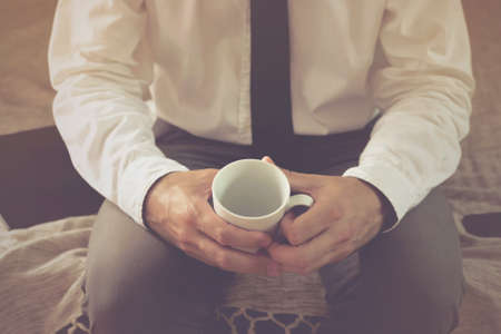 cross process: Lonely businessman in hotel room sitting on the bed and holding empty coffee cup, selective focus cross process toned image. Stock Photo