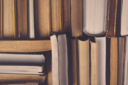 reading book: Stack of Used Old Books in the School Library, Toned Cross Processed Image.