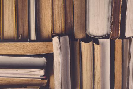 Stack ojetých starých knih v knihovně školy, tónovaný kříž zpracovaný obraz. Reklamní fotografie