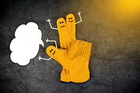 contended: Three Happy Laughing Smileys on Fingers of Yellow Leather Protective Construction Industry Working Gloves with Speech Balloon as Copy Space
