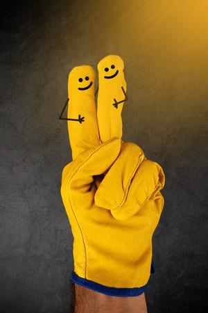 cara sonriente: Dos feliz Riendo emoticonos en los dedos de cuero amarillo Guantes de protecci�n Industria de la Construcci�n de Trabajo Foto de archivo
