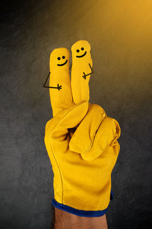 smiley: Two Happy Laughing Smileys on Fingers of Yellow Leather Protective Construction Industry Working Gloves