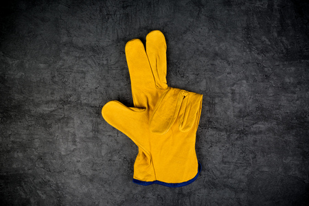 enact: Yellow Leather Construction Engineer or Builder Working Protective Gloves Making Three Fingers Gesture.