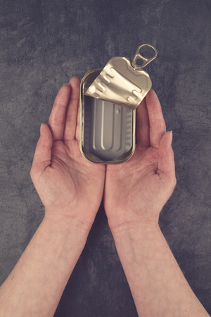 sardine can: Female Hands Holding Open Empty Sardine Fish Tin Can on Grunge Gray Background as Poverty and Hunger Concept, Top View Stock Photo