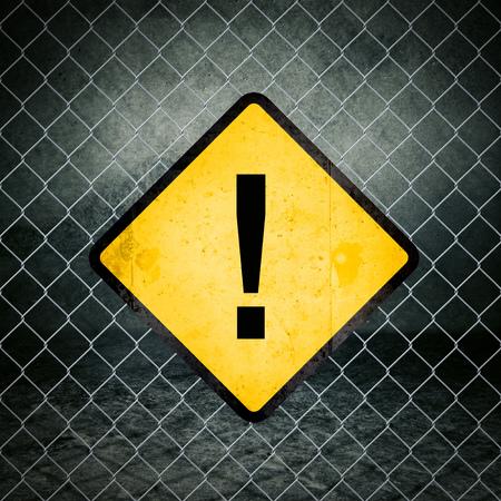 señales de seguridad: Signo de admiración Grunge Señal de peligro amarilla en la cerca de alambre de Nave Industrial